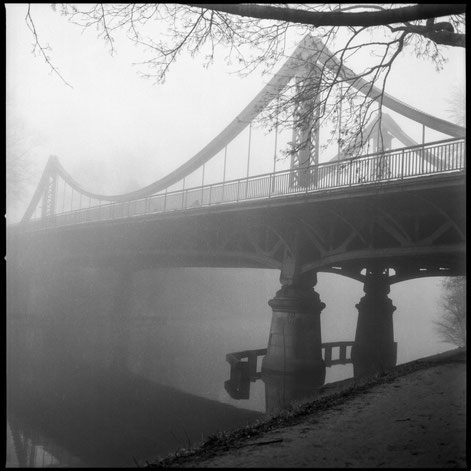 Foggy scene with a river and bridge.