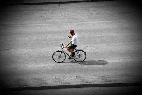 jeune homme à vélo sur son téléphone
