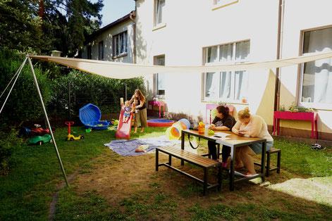 v.l.: Caritas-Mitarbeiterin Daniela Billeci und Bewohnerinnen der Viva-Wohngruppe freuen sich über Innenhofgesteltung im Irmgardishaus I  Foto: Caritas, Larissa Braunöhler