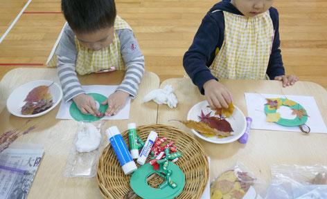 クリスマスの飾りとして、2歳児(母子分離クラス)が、リースの土台に落ち葉をのりで貼っています。