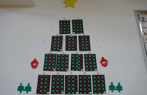 幼稚園児が製作した格子編みの飾りと切り紙を組み合わせて、壁に素敵なクリスマスツリーを作りました。