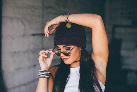 Brünette, junge Frau mit Sonnenbrille und Mütze, rasierte Achseln