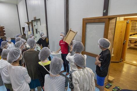 麹室の前で麹蓋を使用した麹造りの説明中。 ※ 麹造りについては、「泉橋酒造の冬」特集内で紹介しています。