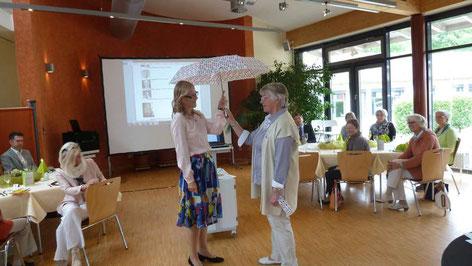 Antje Diller-Wolff hält symbolisch einen Regenschirm in die Luft als Schirmherrin des Leselernhelfer e.V. MENTOR Heidekreis