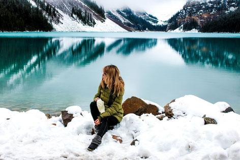 Frau sitzt im Winter am Ufer von einem Bergsee