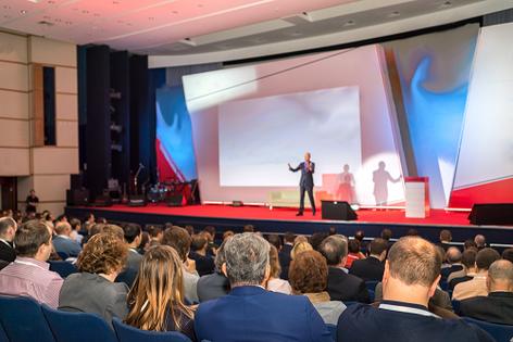 Ein Mann hält eine Rede vor Publikum ohne zu stottern. Hypnose hat geholfen.