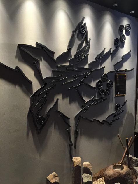 壁に埋め込まれた瓦で絵を作っている。が、これは一体何を表現しているのか?