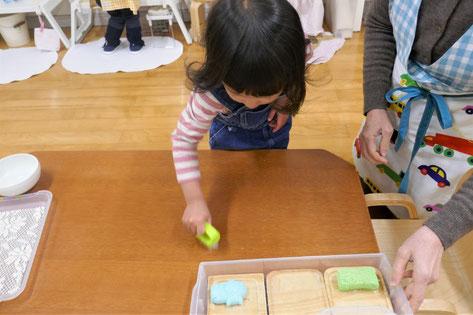 モンテッソーリの個別活動で2歳児がブラシを使ったテーブルを洗う活動を行っています。