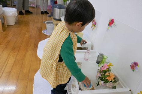 モンテッソーリの日常生活の活動として花を活ける活動を行う中で、水を注ぐために花びんにじょうごをのせています。