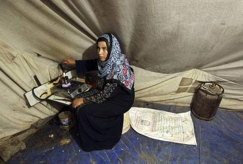 Olfat Qarawi, cuya casa fue destruida durante la ofensiva israelí en Gaza, prepara café en la improvisada vivienda que habita con su familia en un campo para refugiados. Foto Reuters