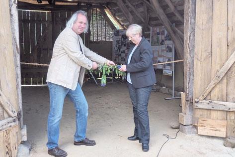Roland Meyer und Jutta Wendland-Park stehen vor dem Eingang zum Schafstall und zerschneiden ein geschmücktes Band.