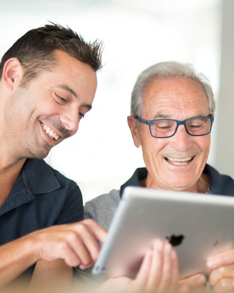 Älterer Herr lacht zusammen mit seinem Betreuer