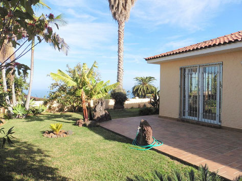 Im Garten stehen Bananen, Palmen und ist eine Rasenfläche um das Haus. Im Hintergrund sieht man das Meer.