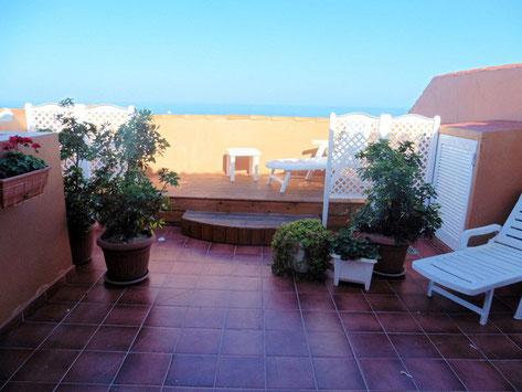 Große geflieste Terrasse mit Gartenmöbel und Pflanzen, sowie Blick auf das Meer.