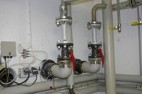 Zwei Isolierflansche mit weißen Rohren oberhalb der Kugelventile in den Fernwärmeleitungen