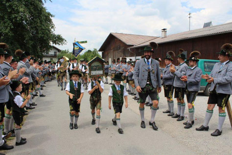 Trachtenvereinsmitglieder marschieren in Bad Ailbing