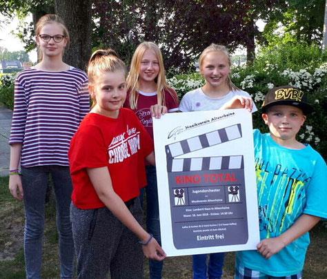 Die Jugendlichen vom Musikverein Altenrheine präsentieren stolz das Plakat zu ihrem Jahreskonzert am 16. Juni