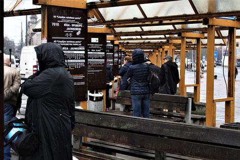 Menschen an einer Bushaltestelle in Riga