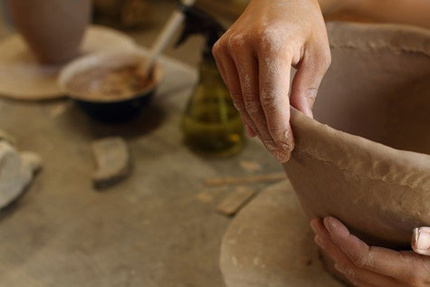 陶芸の成形技法のひとつ、「手びねり」という技法で作っているところ。粘土をひも状に延し、一段ずつ積み上げ形にしていく。