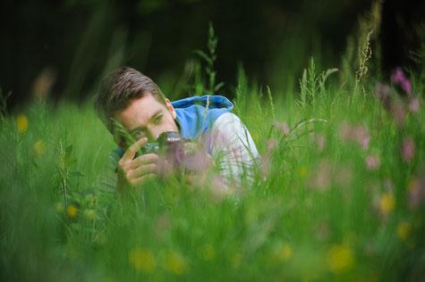 Christian beim Anvisieren eines Motivs in der Blumenwiese