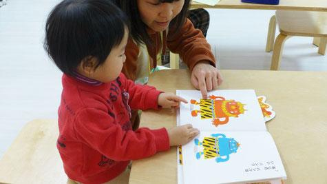 幼児教室バンビーニクレアーレ・モンテッソーリの活動で、2歳児の生徒が絵本「オニのパンツ」を楽しんでいます。
