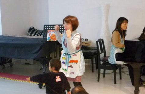 リトミックで、1歳児の生徒が、ピアノに合わせて独自の動きでダンスをしています。