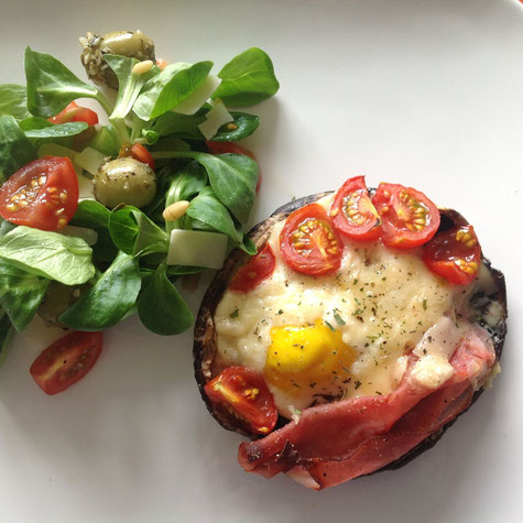 Gevulde portobello met een salade van veldsla, tomaatjes, olijven en Parmezaanse kaas.