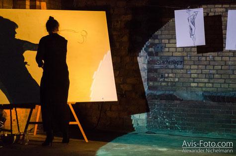 Antje Püpke steht vor einer Staffelei und zeichnet mit Zeichenkohle auf ein großes Bild.