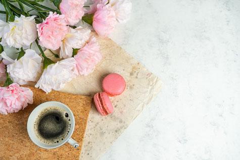 ピンクのノートパソコン、紅茶の入ったカップ&ソーサ。ピンクのバラとガーベラ。