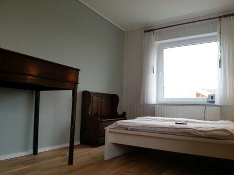Stehpult und Holzbank im Schlafzimmer