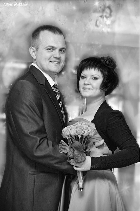 Портрет молодоженов со свадебным букетом в руках у невесты
