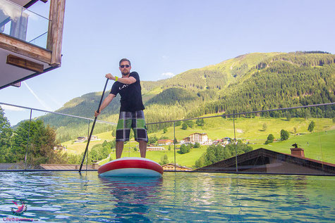Stand up Paddler im Pool vom Adler Resort in Saalbach Hinterglemm