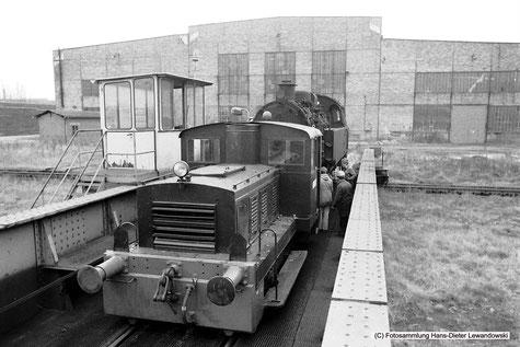"""Lok """"Raubling"""" der gleichnamigen Bayerischen Alpentorfwerke, hat soeben Lok 37 von ihrem zwischenzeitlichen Standplatz vor der östlichen Giebelseite der Lokrichthalle des Bundesbahn Ausbesserungswerkes Braunschweig gezogen."""