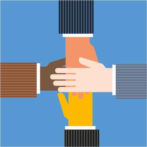 Vier Hände liegen zum Zeichen der Zusammengehörigkeit im Unternehmen übereinander.