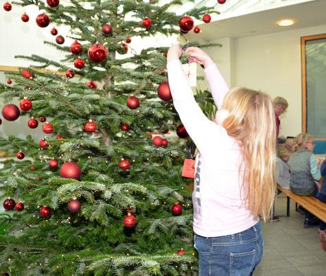 Nele (9) hängt ihren Wunsch in den Wunschbaum.