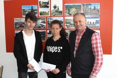 Alexander Raszka und Lea Werwai werden für ihr gutes Abschneiden in der zweiten Runde des Hessischen Mathemaikwettbewerbes von Mathematiklehrer Johann Eisfeld geehrt.