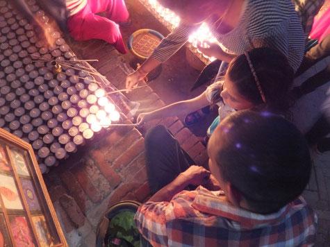 Miriam zündet Kerzen in Bouddha zum Gedenken an die Opfer des Erdbebens an