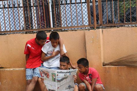 Jungs beim Zeitung lesen