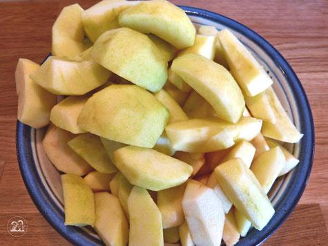 Äpfel für Apfelkuchen geschält und geviertelt in Schüssel
