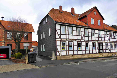 Das ehemalige Schulwohnhaus im Steinweg in unmittelbarer Nähe zur Volksschule (Hintergrund)