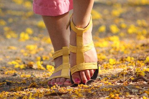 Füsse einer Frau laufen auf einem Teppich bedeckt mit gelben Blüten.