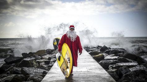 Weihnachten und Surfen - surfender Weihnachtsmann