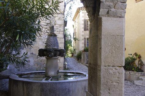 Séguret, der Mascarons Brunnen und eine gepflasterte Gasse.