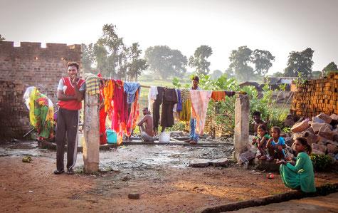 Vater und Kinder vor Wäscheleine und Hausmauer am Lehmboden in Indien