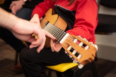 Kind spielt Gitarre in der Musikschule München Schwabing - Münchner Klangwelt