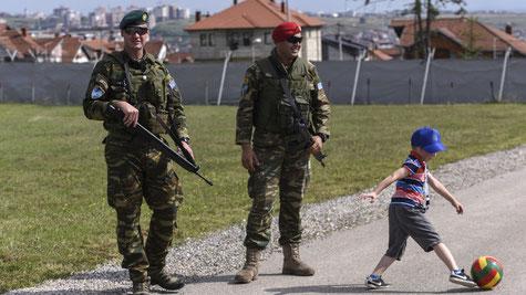 NATO-Soldaten patrouillieren neben spielenden Kindern in Kosovo. Bald wird der gesamte Westbalkan mit NATO-Basen bestückt sein, mit Serbien als bisher einziger Ausnahme.