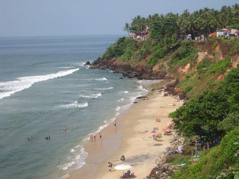 Strand mit Meeresbrandung, darüber ein palmenbewachsenes Kliff.