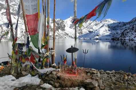 Gebetsfahnen mit Götterstatue, im Hintergrund See und schneebedeckte Berge.