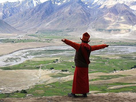 Mönch mit ausgestreckten Armen blickt auf ein Tal im Himalaya. Foto: Maria Frotschnig