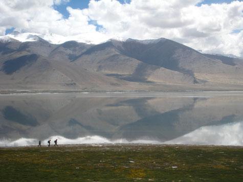Drei Wanderer am Seeufer, dahinter sandfarbige Berge